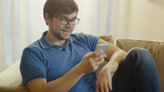 Man is Sitting on Couch and Having Video Chat on Phone. Stock Footage