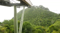 Cable car gondola departs from middle station, rainforest mountains Stock Footage