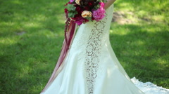 wedding dress with train. wedding bouquet of flowers in hands of young bride. - stock footage