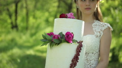 Beautiful bride holding a wedding cake with a flowers Outdoors Stock Footage