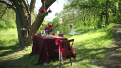 Outdoor Wedding table decorations and young bride in the park - stock footage
