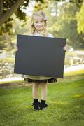 Cute Little Blonde Girl Holding a Black Chalkboard Outdoors. - stock photo