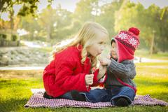 Little Girl with Baby Brother Wearing Coats and Hats Outdoors. - stock photo