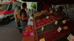 Street vendor weighs fruit for customer Munich Stock Footage