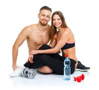 Athletic couple - man and woman after fitness exercise with dumbbells and bot Stock Photos