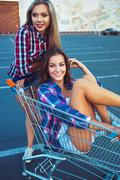 Two happy beautiful teen girls driving shopping cart outdoors Stock Photos