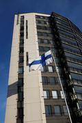 Fluttering national flag of Finland beside modern building Stock Photos