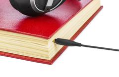 Headphones and book isolated on white background Stock Photos