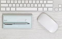 Blank checkbook on white desktop with pen and mouse Stock Photos