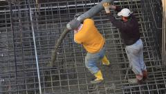 Two workers pulling the large hose of a concrete pumping machine for concreting Stock Footage