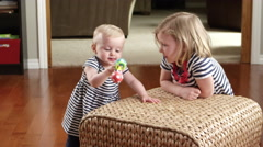 Little girl and baby playing on a wicker stool Stock Footage