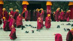 Monks gather outside of Grand Sutra Hall at Labrang Monastery, China Stock Footage