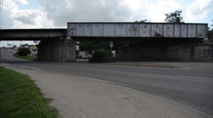 Wide static shot of a train bridge over the road with grafitti that says Cool - stock footage