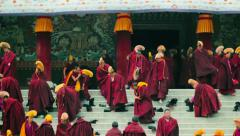 Monks put on shoes after prayers at Labrang Monastery, China Stock Footage