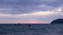 Tourists kayaking in dusk, incredible sky colours, sunset afterglow purple cloud Stock Footage