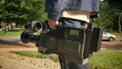 Cameraman Carrying BetaCam SP Camera Outside Stock Footage
