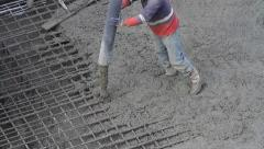 Workers working on construction site, a laborer pulling the hose tor concreting Stock Footage