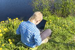 Ten year boy with laptop on riverside in summer Stock Photos