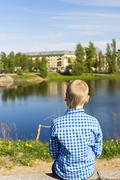 Ten year boy looks on city from river shore - stock photo