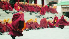 Monks sit on stairway outside the Grand Sutra Hall at Labrang Monastery, China Stock Footage