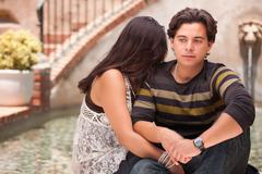 Attractive Hispanic Couple During A Serious Moment at a Fountain. - stock photo