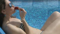 Hot woman eating strawberry near swimming pool, seducing, flirt Stock Footage