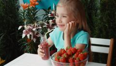 Girl drinking strawberry juice and looking at camera Stock Footage