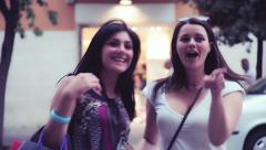 Two excited girls crossing street looking shop in city Stock Footage