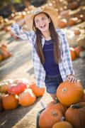 Preteen Girl Playing with a Wheelbarrow at the Pumpkin Patch. Stock Photos