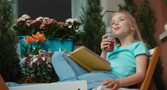 Girl sitting on the balcony and reading a book Stock Footage