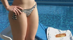 Female lower body, attractive woman getting tan by the pool Stock Footage