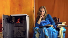 Woman read book at home near warm stove fire place on winter day Stock Footage