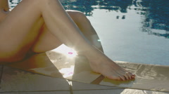 Attractive female legs playfully splashing water out of the pool Stock Footage