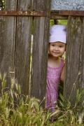 Little girl  playing peek a boo through a gap in a broken plank in a rustic w Stock Photos