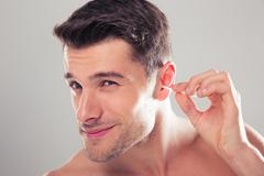 Man cleans his ear with a cotton swab - stock photo