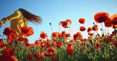 Beautiful girl with long hair having fun outdoors in the poppies field. Slow - stock footage