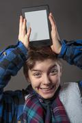 Smiling mad boy holding a tablet computer on his head Stock Photos