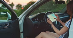Woman using digital tablet in the car. Reading road map and navigation Stock Footage