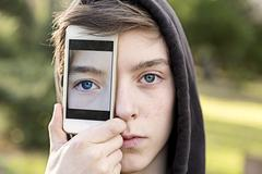 virtual realty, teenage boy holding a smart phone in front of his face - stock photo