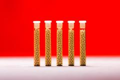 Five small glass tubes with homeopathy globules, red background Stock Photos