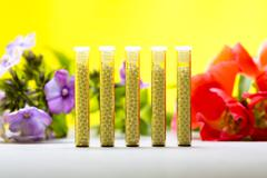 five small glass tubes with homeopathy globules, yellow background and flower - stock photo