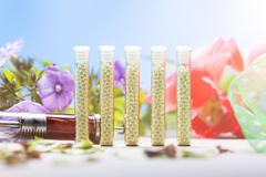 Small glass tubes with homeopathy globules, syringe and flowers Stock Photos