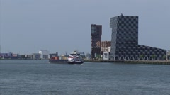 Sea vessel passing the Headquarters of STC group Lloyd District, ROTTERDAM Stock Footage