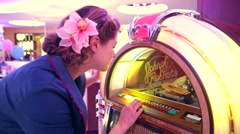 Woman chose melody from Johnny Rockets jukebox. Stock Footage