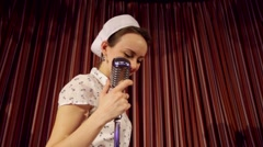 Retro girl singing to microphone Stock Footage
