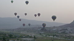 Multi-colored balloons fly over rocks.Greatest tourist attraction of Cappadocia Stock Footage