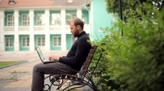 Stock Video Footage of The Young Man Working on a Laptop in the Beautiful Residence