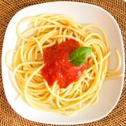 Italian spaghetti dish with tomatoes and basil - stock photo