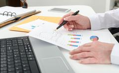 Businesswoman working on financial graphs Stock Photos