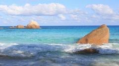 Waves breaking on granite boulders in beach of Anse Lazio Stock Footage